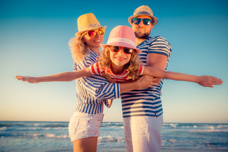man flying: Happy family on the beach. People having fun on summer vacation. Father, mother and child against blue sea and sky background. Holiday travel concept