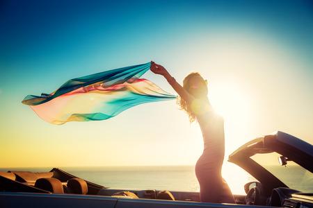 Silhouet van een jonge vrouw op het strand. Meisje met vliegende stof tegen zonsondergang hemel en zee achtergrond. Vrouw met de auto reist. Zomer vakantie en reizen concept Stockfoto - 78757096