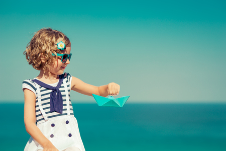 happy holidays: Happy child with paper sailing boat. Kid having fun on summer vacation. Travel and adventure concept Stock Photo