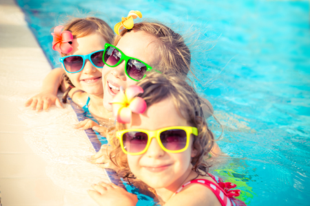 happy holidays: Happy children in the swimming pool. Funny kids playing outdoors. Summer vacation concept