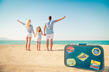 aspirational: Happy family on the beach. People having fun on summer vacation. Father, mother and child against blue sea and sky background. Holiday travel concept