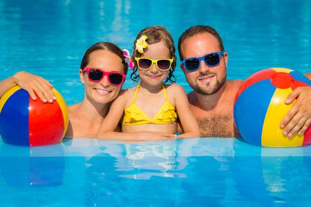 夏休みに楽しい幸せな家族。父、母と子のスイミング プールで遊んで。アクティブな健康的なライフ スタイル コンセプト