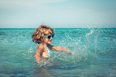 1 person: Happy child playing in the sea. Kid having fun at the beach. Summer vacation and active lifestyle concept