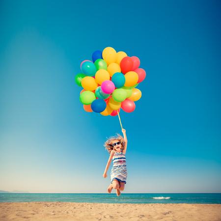 Gelukkig kind springen met kleurrijke ballonnen op zandstrand. Portret van grappig meisje tegen blauwe zee en hemelachtergrond. Actief kind met plezier op zomervakantie. Vrijheid en verbeeldingskoncept Stockfoto
