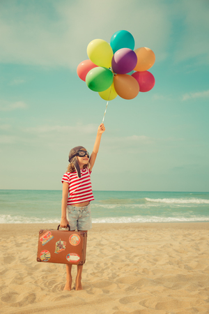 Happy child playing with toy air balloons against sea and sky background. Kid pilot having fun outdoor. Summer vacation and travel concept. Freedom and imagination