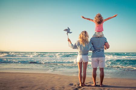 Familia feliz en la playa. Gente que se divierte en vacaciones de verano. Padre, madre y niño contra el fondo azul del mar y del cielo. Concepto de viajes de vacaciones Foto de archivo