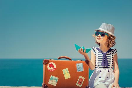 ヴィンテージ スーツケースを持って幸せな子。子供の夏休みに楽しい時を過します。旅行や冒険のコンセプト 写真素材