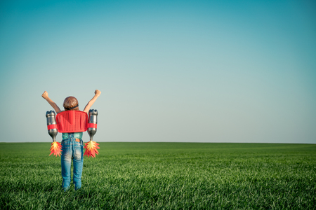Kid with jet pack outdoor. Child playing in green spring field. Success, imagination and innovation technology concept. Summer travel and adventure Stockfoto