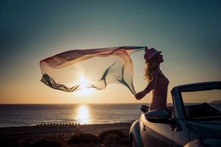 voyage: Silhouette of young woman at the beach. Girl with flying fabric against sunset sky and sea background. Female traveling by car. Summer vacation and travel concept