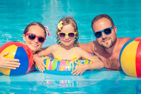 Glückliche Familie, die Spaß auf Sommerferien hat. Vater, Mutter und Kind spielen im Schwimmbad. Aktives gesundes Lifestyle-Konzept Standard-Bild - 80327387