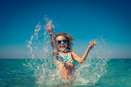 Happy child playing in the sea. Kid having fun at the beach. Summer vacation and active lifestyle concept 免版税图像 - 80327397
