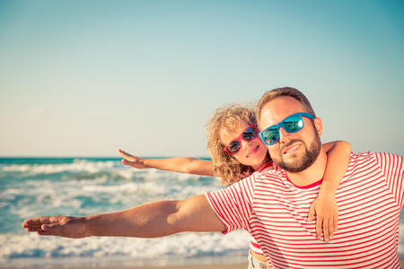 Happy family on the beach. People having fun on summer vacation. Father and child against blue sea and sky background. Holiday travel concept photo