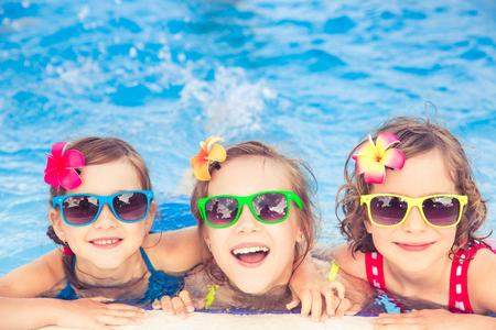 スイミング プールで幸せな子供たち。面白い子供たちが野外で遊ぶ。夏の休暇の概念 写真素材 - 80327399