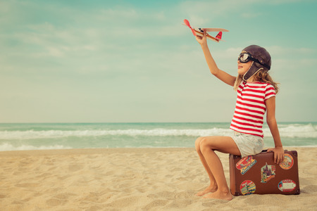 Happy child playing with toy airplane against sea and sky background. Kid pilot having fun outdoor. Summer vacation and travel concept. Freedom and imagination