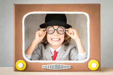 Child playing with cardboard box TV. Kid having fun at home. Communication concept Stock Photo - 83655733