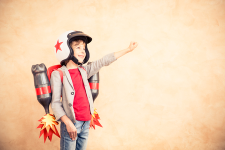 Kid with jet pack. Child playing at home. Success, imagination and innovation technology concept