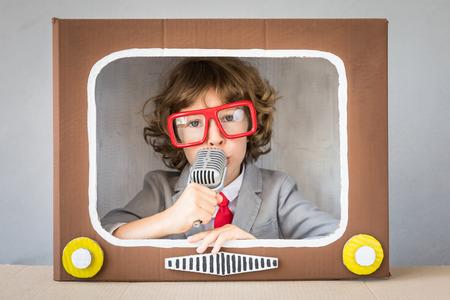 Enfant jouant avec une boîte en carton TV. Enfant s'amuser à la maison. Concept de communication