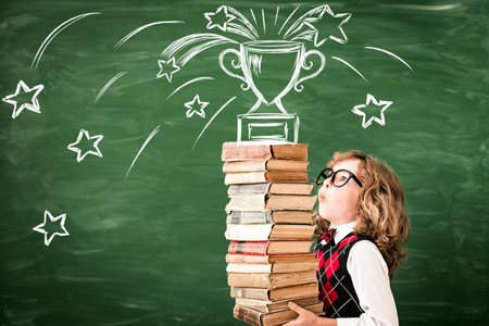 Portrait of child in classroom against chalkboard. Kid with books in class. Success, idea and win concept. Back to school