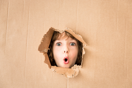 Portrait of worried child looking through hole of cardboard. Copy space for your text photo