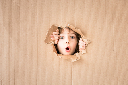 Portrait of surprised child looking through hole of cardboard. Copy space for your text