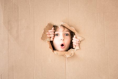 Portret van verrast kind dat door karton gaat kijken. Kopieer de ruimte voor uw tekst Stockfoto