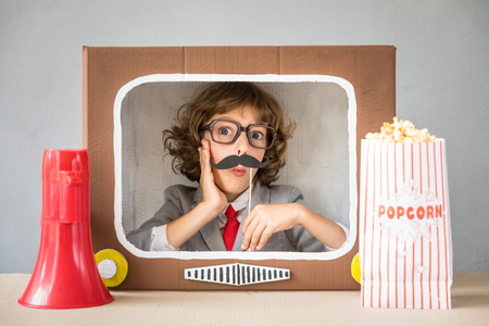 Child playing with cardboard box TV. Kid having fun at home. Communication concept photo
