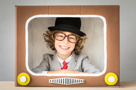 funny glasses: Child playing with cardboard box TV. Kid having fun at home. Video blogging concept Stock Photo