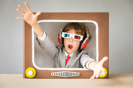 Child playing with cardboard box TV. Kid having fun at home. Video blogging concept Zdjęcie Seryjne