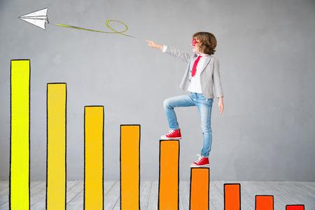Kind gibt vor, Geschäftsmann zu sein. Kid steigt auf gezogene Chart Bar. Phantasie, Idee und Erfolgskonzept. Kopiere Platz für deinen Text Standard-Bild