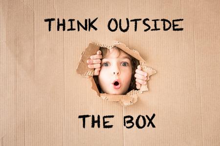 """Überraschtes Kind sucht durch Loch aus Karton. """"Denken Sie außerhalb der Box"""" Text"""
