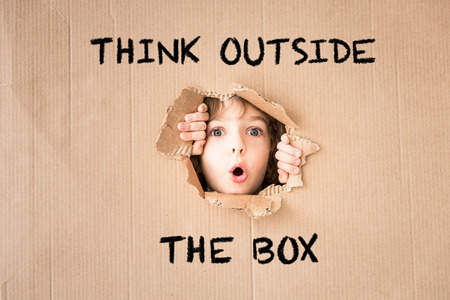 Verrast kind kijkt door het gat van karton. Tekst 'Think outside the box'