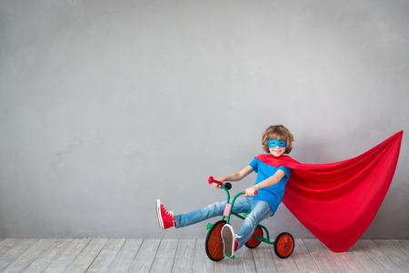 Child pretend to be superhero. Kid playing at home. Success, creative and imagination concept