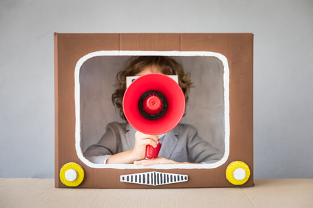 Child playing with cardboard box TV. Kid having fun at home. Video blogging concept Stock Photo
