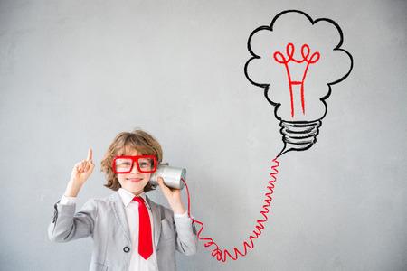 ビジネスマンのふりをする子。子供が自宅で再生します。想像力、アイデア、コンセプトを開始。学校に戻る 写真素材