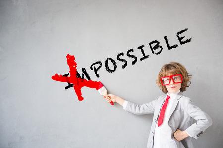ビジネスマンのふりをする子。子供の「不可能」のテキストを消去します。想像力、アイデア、成功のコンセプトです。テキストのコピー スペース