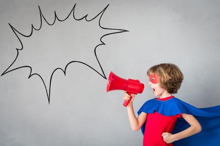 子供のスーパー ヒーローのふりをします。スーパー ヒーローの子供が自宅で再生します。想像力と勝者の概念 写真素材