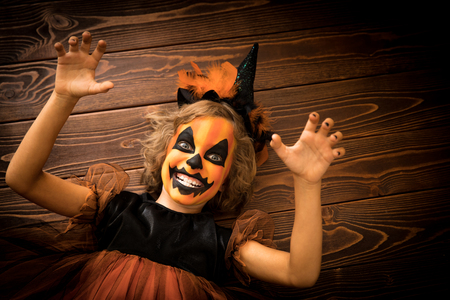 black: Funny child dressed witch costume. Kid painted terrible pumpkin. Halloween autumn holiday concept