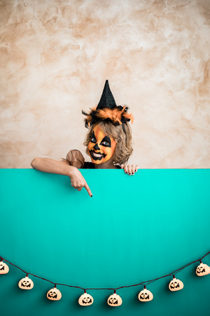 Funny child dressed witch costume. Happy kid painted terrible pumpkin holding banner blank. Halloween autumn holiday concept