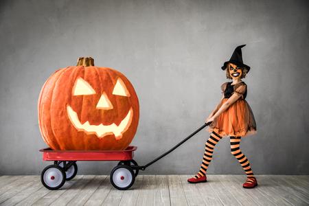 Costume da strega vestito da bambino divertente. Kid ha dipinto una zucca terribile. Concetto di vacanza autunnale di Halloween