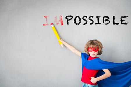 Het kind beweert superheld te zijn. Superheldjongetje wist tekst ONMOGELIJK. Verbeelding, creativiteit en winnaarsconcept Stockfoto