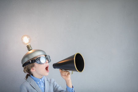 Chico inteligente en el aula. Niño con auriculares de realidad virtual de juguete en clase. Éxito, idea y concepto creativo. De vuelta a la escuela