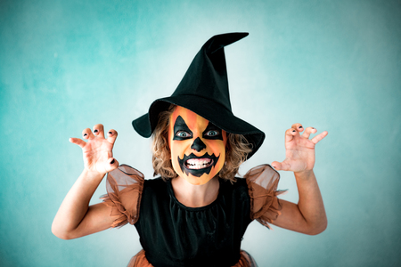 Funny child dressed witch costume. Kid painted terrible pumpkin. Halloween autumn holiday concept