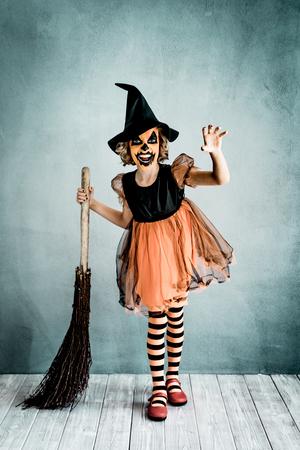 Grappig kind gekleed heks kostuum. Jong geverfde vreselijke pompoen. Halloween herfstvakantie concept