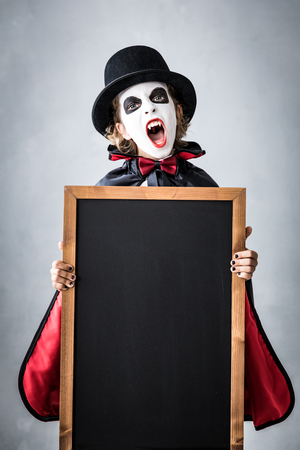 Funny child dressed Halloween costume. Kid painted terrible vampire holding banner blank. Autumn holiday concept