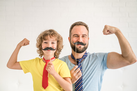 Funny man and kid with fake mustache. Happy family playing in home 스톡 콘텐츠