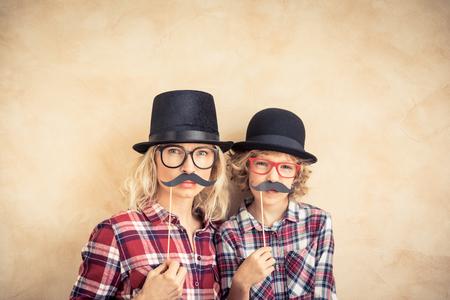 面白い女は、偽の口ひげを持つ子供。幸せな家族の家で遊ぶ
