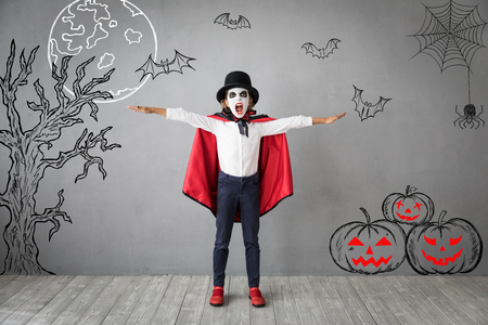 Funny child dressed Halloween costume. Kid painted terrible vampire. Autumn holiday concept 版權商用圖片