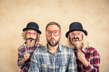 Funny man, woman and kid with fake mustache. Happy family playing in home Standard-Bild