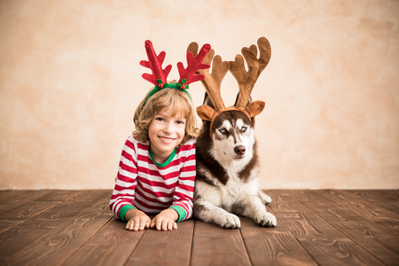 Happy child and dog on Christmas eve. Kid and pet dressed in Santa hat. Girl having fun with husky at home. Stockfoto