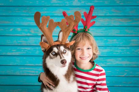 幸せな子とクリスマスイブの犬。子供やペットは、サンタ クロースの帽子に身を包んだ。女の子ハスキーを家庭で楽しんで。中国暦新年コンセプト